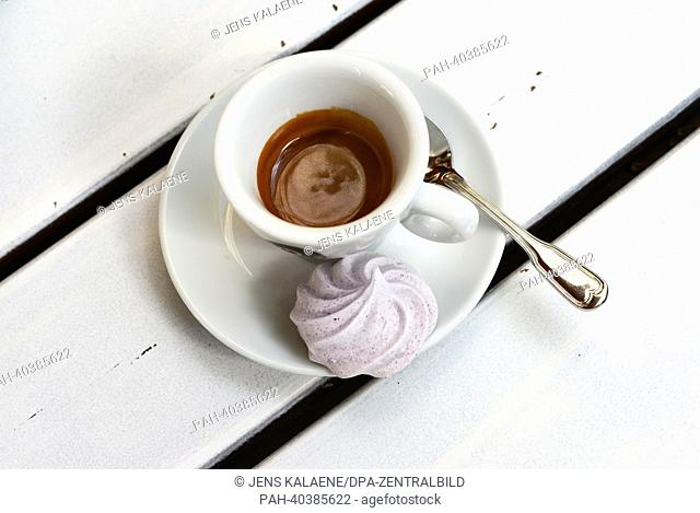 A cup of espresso and a meringue are pictured on a wooden table in Berlin, Germany, 7June 2013. Photo: Jens Kalaene   usage worldwide