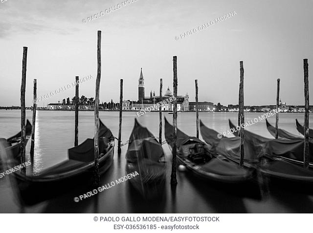 Moving Gondolas on Venice waterfront, San Giorgio Maggiore on the background