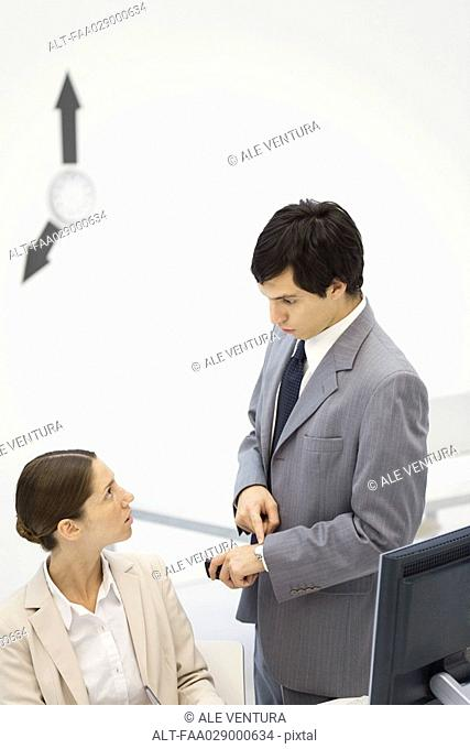 Male supervisor standing beside female employee, pointing at wristwatch, clock hands on wall in background