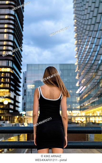 Rear view of young woman wearing black dress in the city at dusk