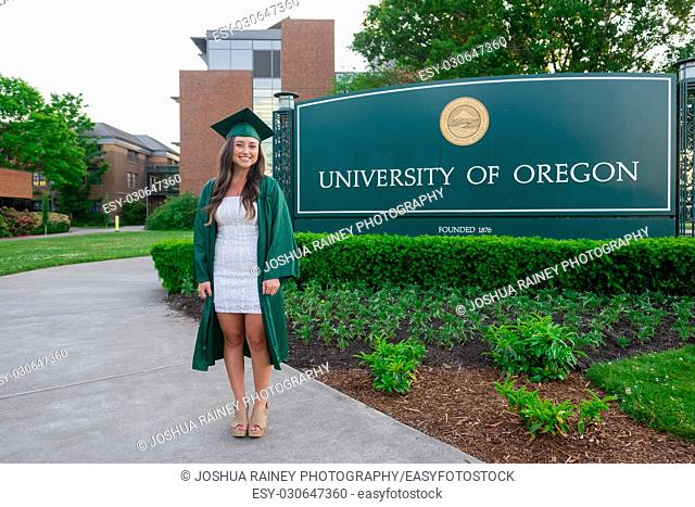 EUGENE, OR - MAY 22, 2017: Female college student poses for graduation photos at the main entrance sign on campus at the University of Oregon in Eugene