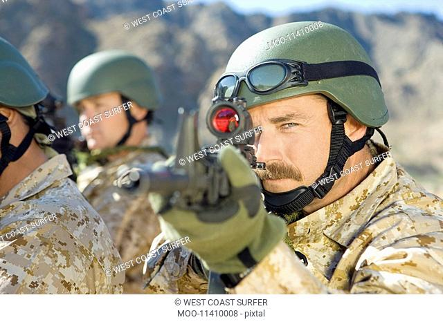 Soldier aiming rifle outdoors close-up