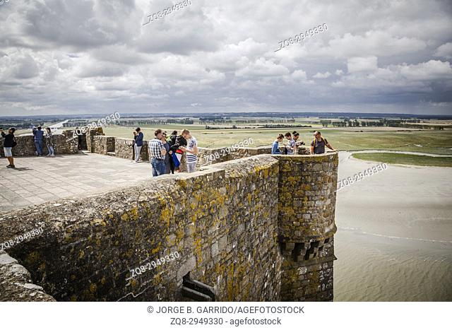 People visiting Mont Saint Michel monastery, Brittany, France enjoying the view from the famous island commune, Le Mont Saint Michel's balcony
