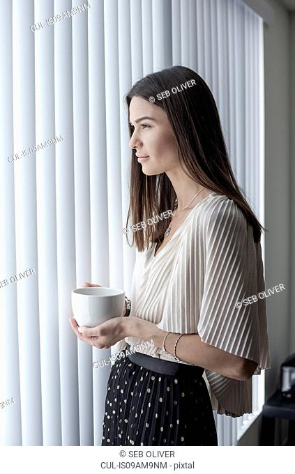 Young woman looking out of window with coffee