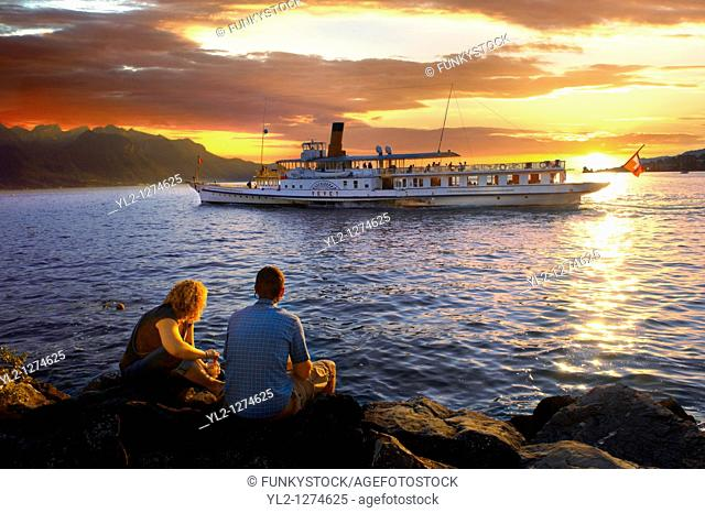 Youg couple watching a ferry at sunset on Lac Leman lake Geneva - Montraux Switzerland