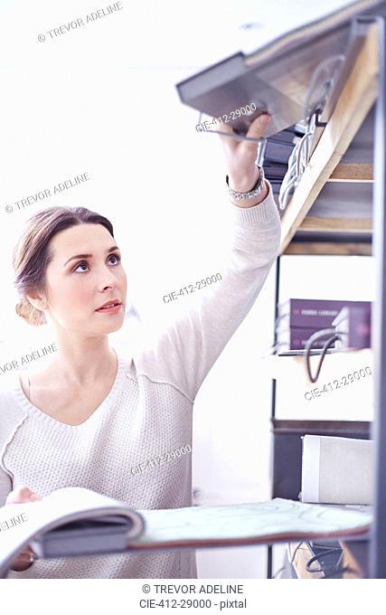 Interior designer reaching for swatch book on shelf
