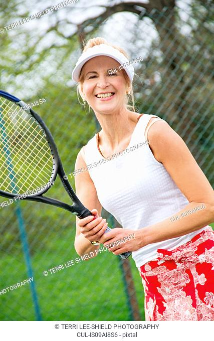 Portrait of mature woman playing tennis