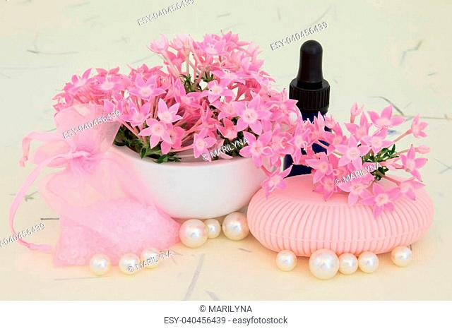 Verbena flowers with aromatherapy essential oil bottle, pink soap, bath crystals and pearls over mottled cream background
