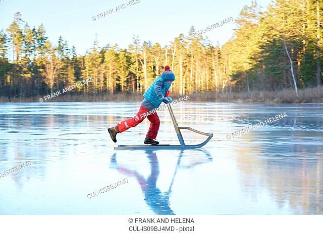 Boy skating on sleigh across frozen lake