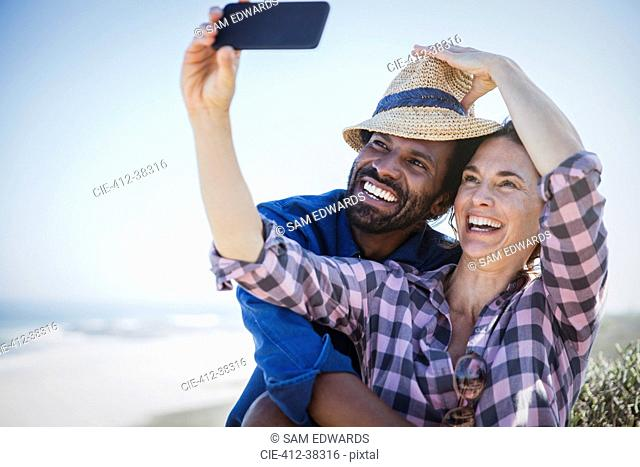 Playful, smiling multi-ethnic couple taking selfie with camera phone on sunny summer beach