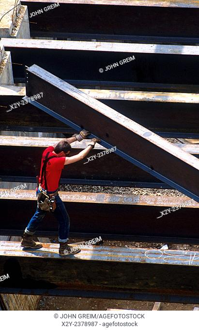 Overview of a construction worker guiding a steel beam on a commercial building work site