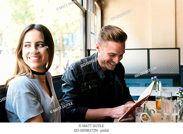 Young couple sitting in bar, looking at menu