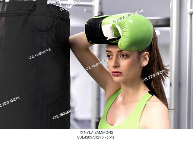 Portrait of a young woman at gym leaning against punchbag wearing boxing glove