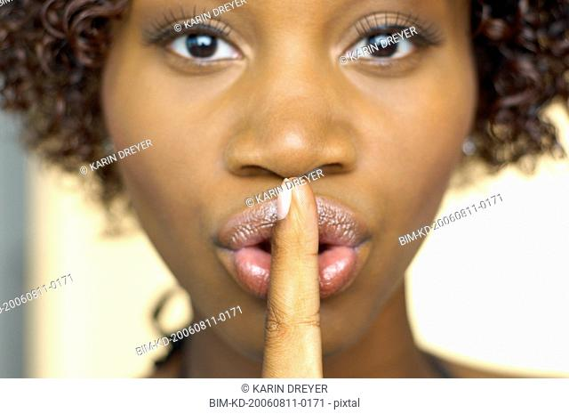 Close up of African woman with finger up to lips
