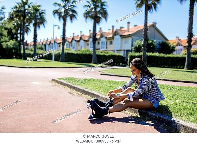 Spain, Gijon, teenage girl sitting on curb tying her roller skates
