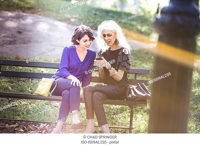 Young woman in city park with mentor looking at photos in smartphone