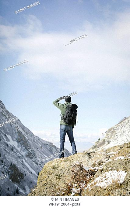 A man hiking in the mountains standing on an outcrop looking at the view