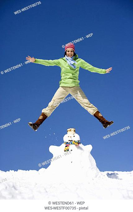 Austria, teenage girl (16-17) jumping on snowman, smiling, low angle view