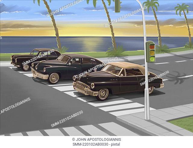 Three vintage black cars waiting at traffic light