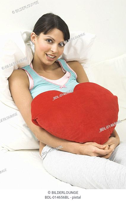 portrait of young woman lying in bed holding red cushion in shape of heart