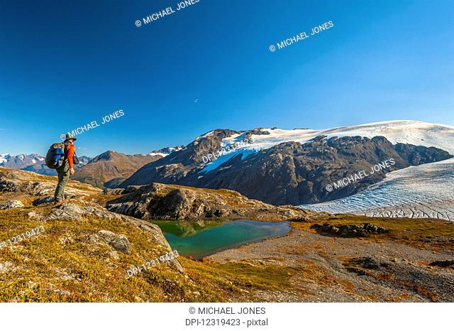 A man hiking near an unnamed lake near the Harding Icefield Trail in Kenai Fjords National Park on a summer day, South-central Alaska; Alaska