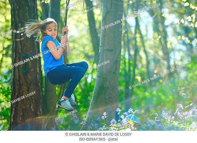 Girl swinging through tree's in bluebell forest, Hallerbos, Brussels, Belgium