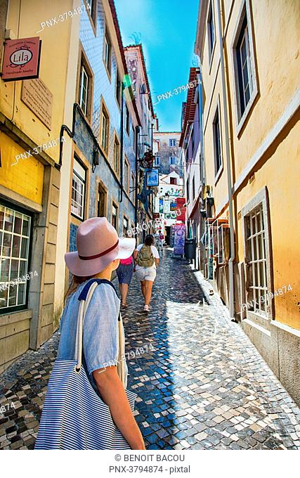 Young woman back looks to an alley in the town of Sintra, Lisbon area, Portugal