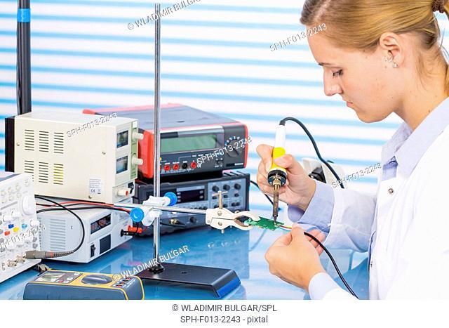 Female technician working on circuit board
