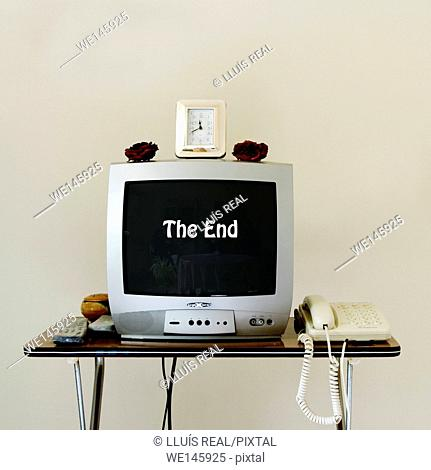 """Old TV set, telephone and clock on folding table. """"The end"""" can be sen on the screen"""