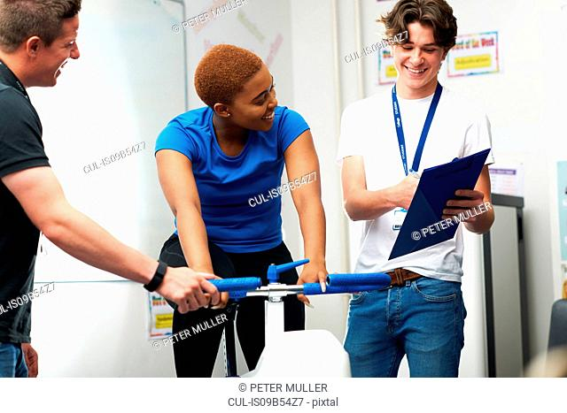 Young woman on exercise bike, young man assessing fitness levels