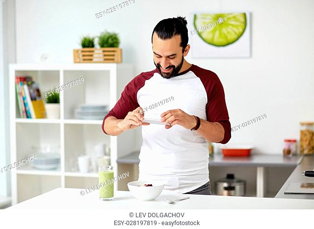 vegetarian food, healthy eating, people, technology and breakfast concept - man with smartphone photographing muesli with vegetable smoothie at home kitchen