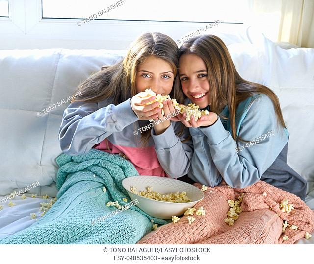 best friend girls at sofa having fun with popcorn watching movie