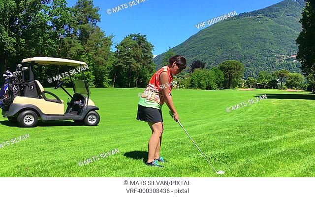 Woman Playing Golf on Fairway with Her Golf Cart in Switzerland