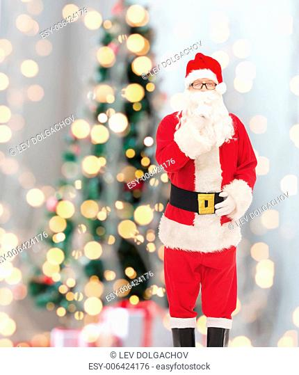 christmas, holidays and people concept - man in costume of santa claus making hush gesture over tree lights background