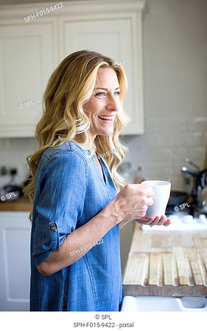 MODEL RELEASED. Woman in kitchen with hot drink, portrait