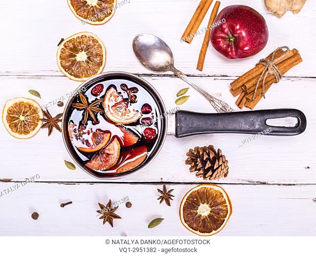 mulled wine with spices and fruits in an aluminum container on a white wooden background, top view