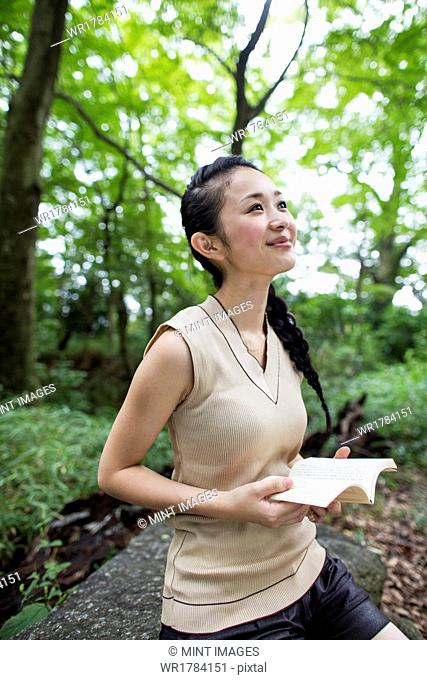 Young woman holding a book in a forest