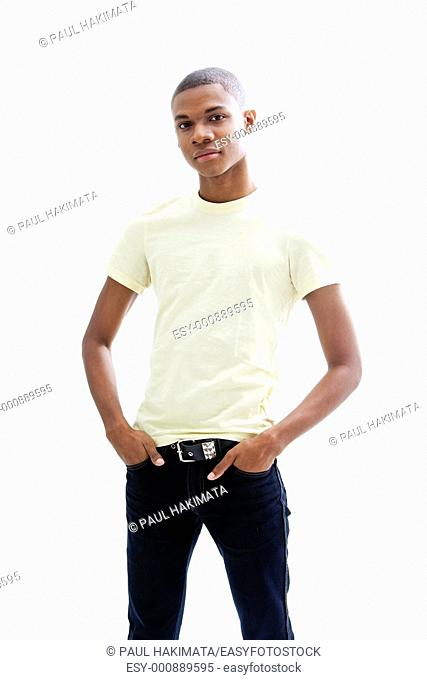 Casual young African man in yellow shirt and hands in pocket of jeans, isolated