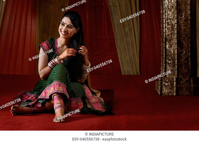 Full length of smiling Indian bride sitting while looking away
