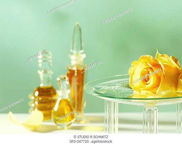 Aroma lamp with rose, flacons in background