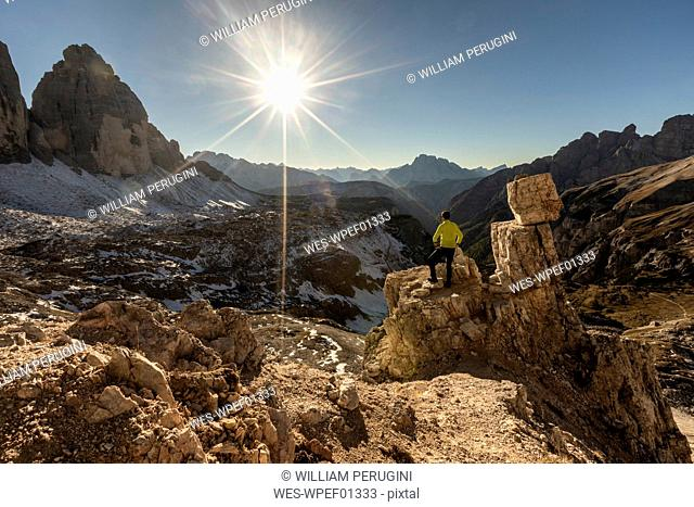 Italy, Tre Cime di Lavaredo, man hiking and looking at the valley with peaks and sun over the horizon