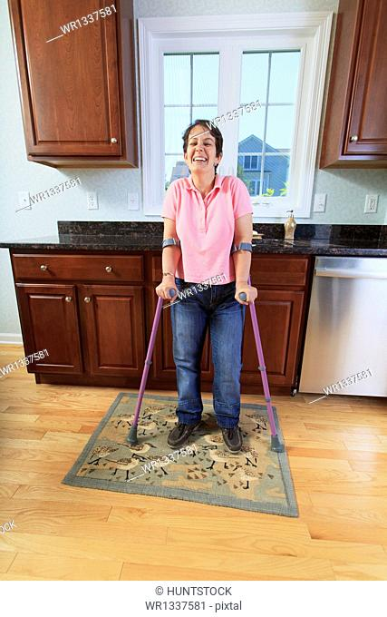 Woman with cerebral palsy using her crutches and smiling in kitchen