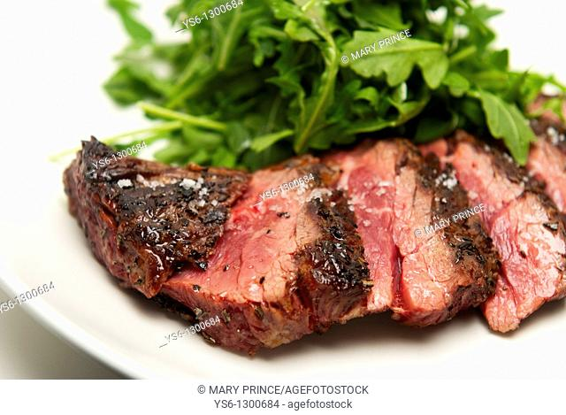 Rare Sliced Steak and Arugula on a White Plate