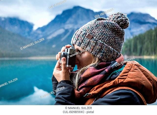 Woman taking photograph of view, Emerald Lake, Yoho National Park, Field, British Columbia, Canada