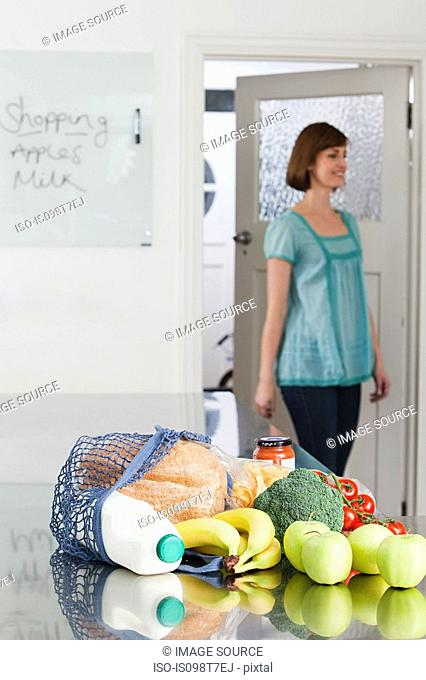 Woman and groceries in kitchen