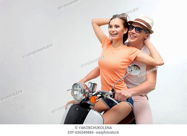 Portrait of cheerful young lovers driving the scooter with joy. The woman is sitting before her boyfriend and embracing him with love