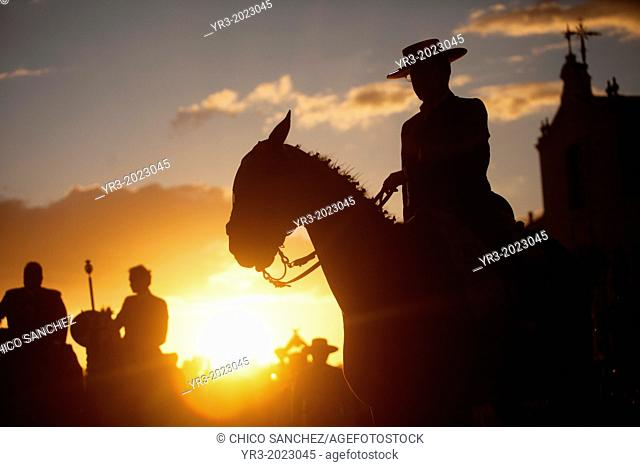 A pilgrim wearing a Spanish hat rides his horse at sunset during the pilgrimagein front of the shrine of the Virgin of Rocio, in Almonte, Donana National Park