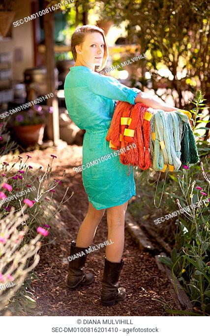 Woman with basket of yarn standing in garden