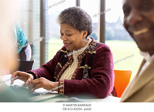 Smiling, confident senior businesswoman using laptop