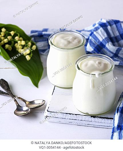 glass jars with homemade yogurt on a white wooden board, close up